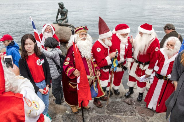 People dressed as Santa Claus take take part in the World Santa Claus Congress, an annual event held every summer at the amusement park Dyrehavsbakken, in Copenhagen